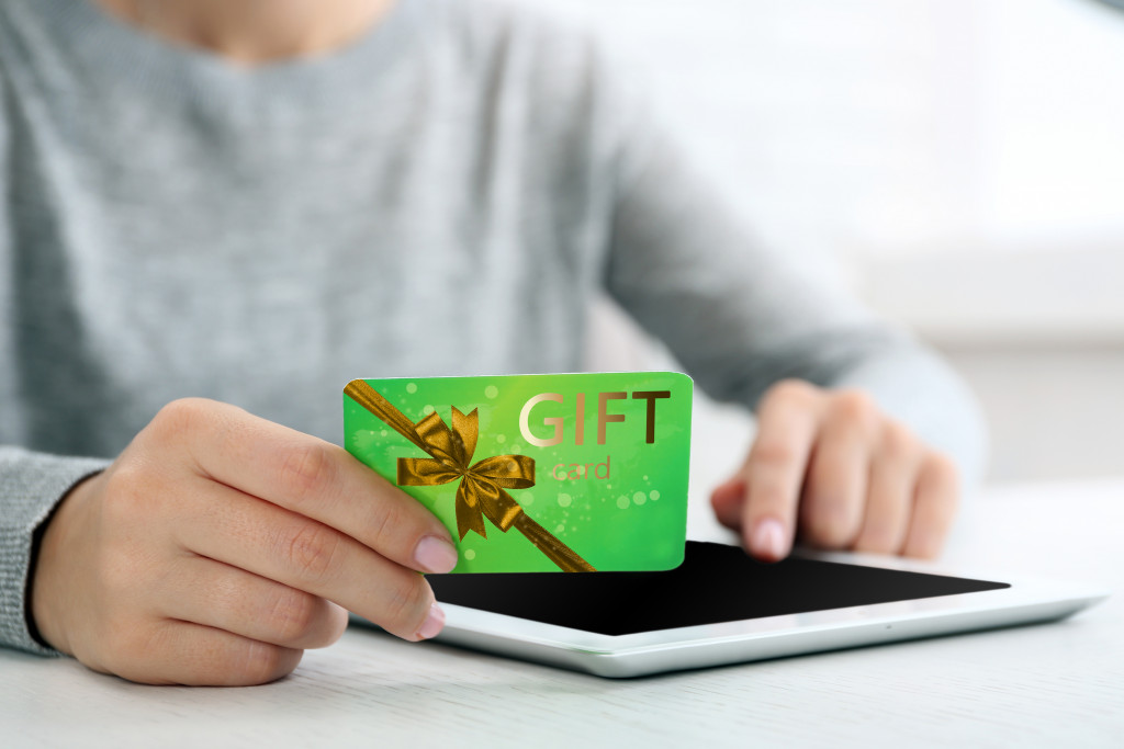 man holding gift card over tablet